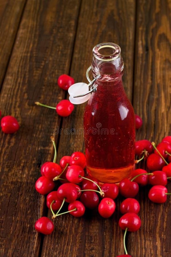 在瓶的红色樱桃饮料在果子中间 图库摄影