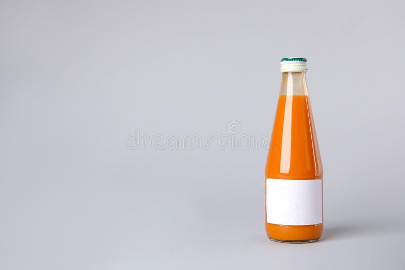 在瓶的鲜美饮料有在颜色背景的空白的标签的 库存图片