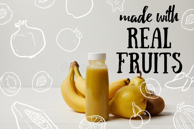 在瓶的黄色戒毒所圆滑的人用香蕉、梨和猕猴桃在白色背景,做用真正 库存图片