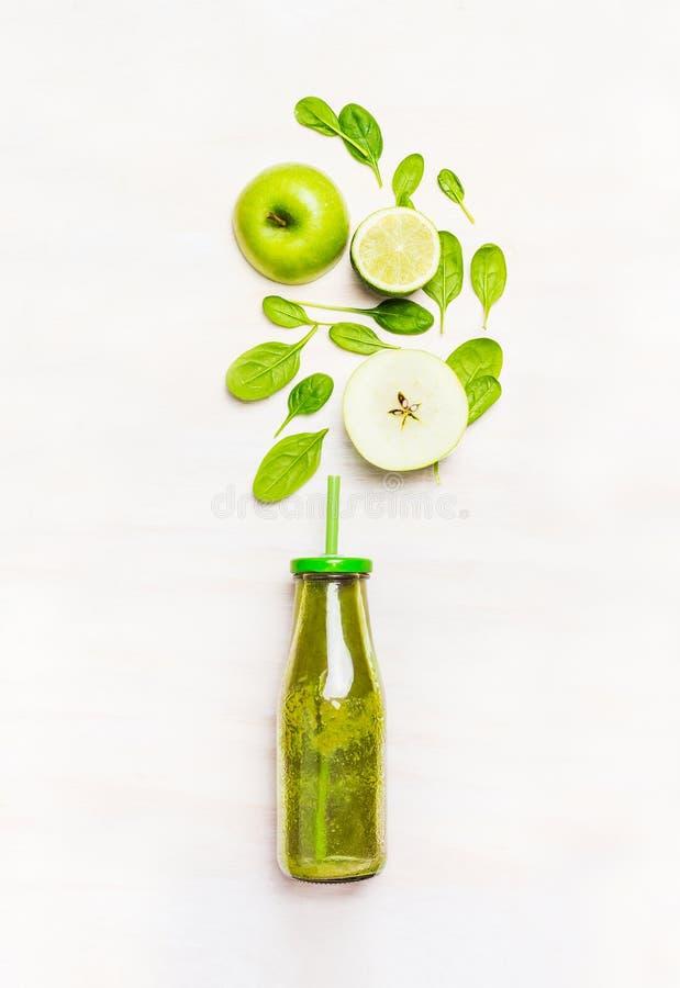 在瓶的绿色圆滑的人饮料有秸杆和成份的(菠菜、苹果,石灰)在白色木背景 免版税库存图片