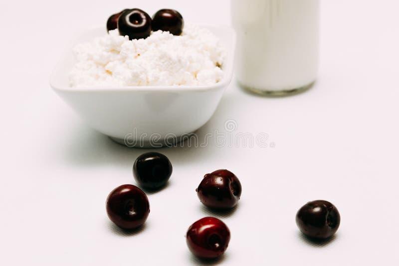 在瓶酸奶干酪和樱桃莓果的牛奶在白色背景 免版税库存照片