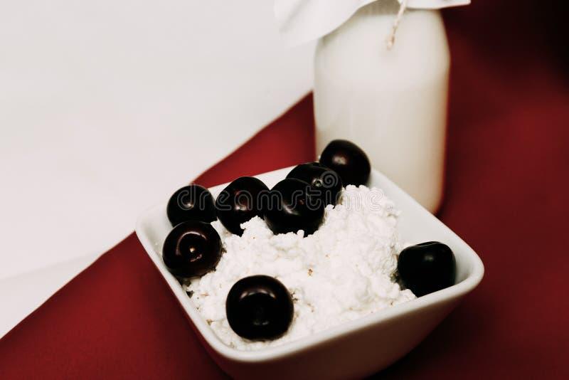 在瓶酸奶干酪和樱桃莓果的牛奶在红色和白色背景 图库摄影