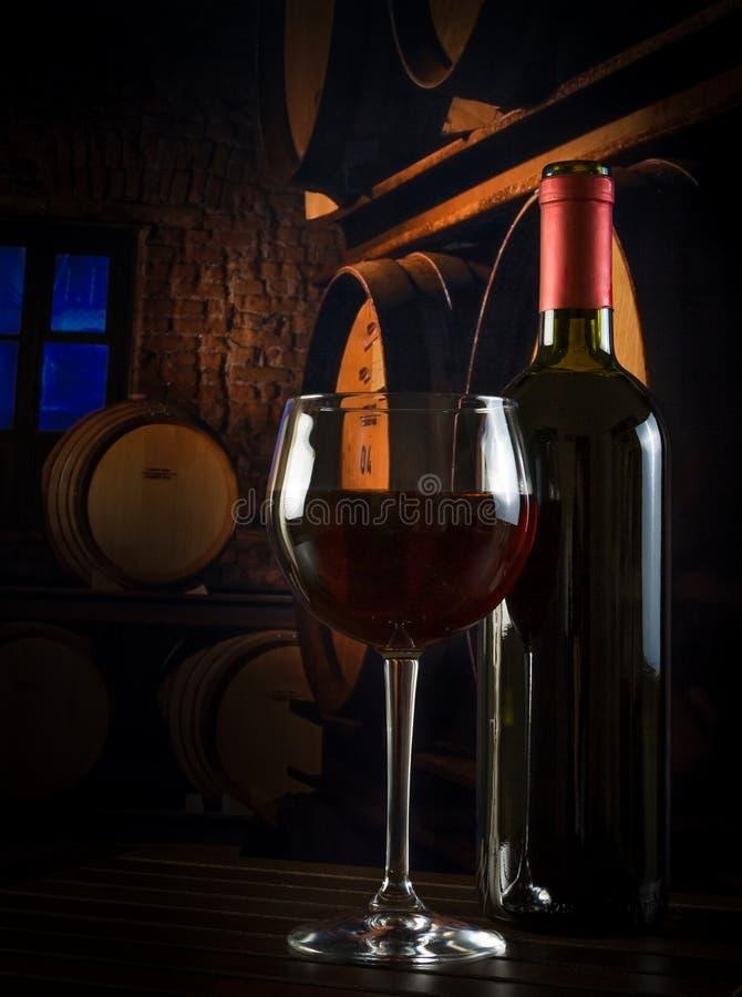 在瓶附近的酒杯在老葡萄酒库里 库存照片