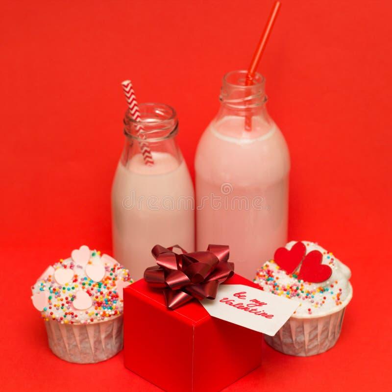 在瓶鸡尾酒秸杆,逗人喜爱的杯形蛋糕,礼物盒的桃红色草莓奶昔 库存照片
