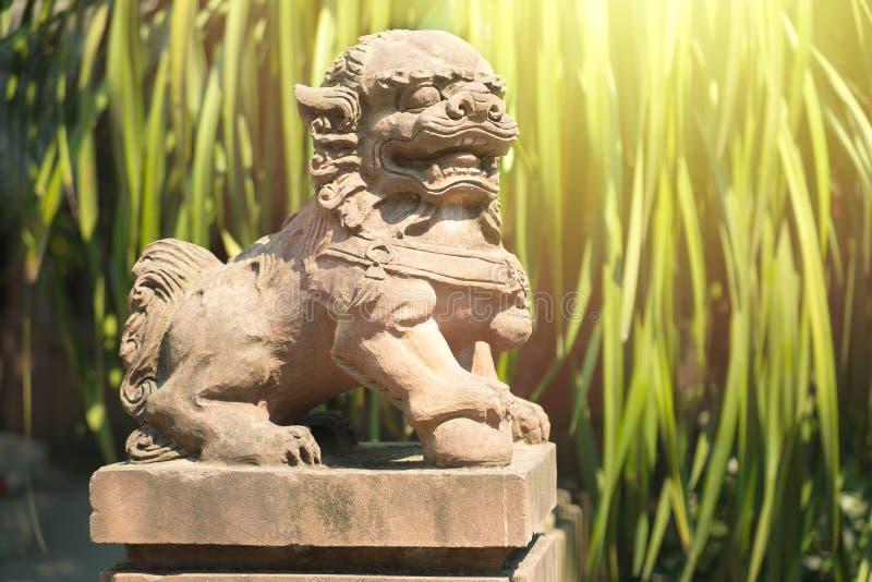 在瓷寺庙的中国狮子雕象与绿色的生叶backgroud 免版税图库摄影