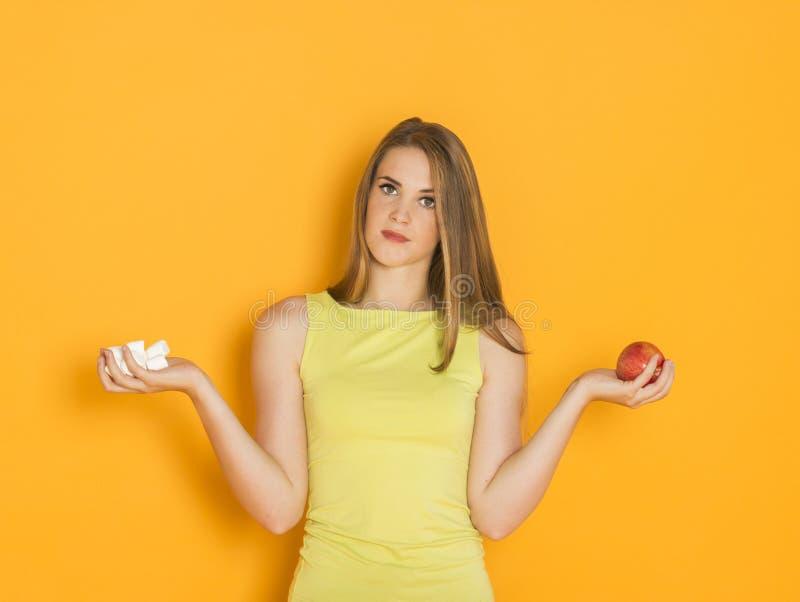在甜点和健康食物之间的困难的选择 图库摄影
