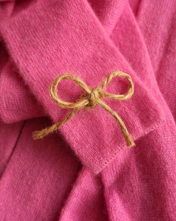 在生动的桃红色开士米长袍的麻线弓 免版税库存照片