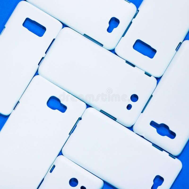 在生动的蓝色背景的白色电话盒 流动论点或智能手机保护者您的设计的 免版税库存图片