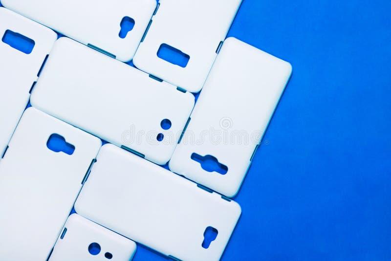 在生动的蓝色背景的白色电话盒 流动论点或智能手机保护者您的设计的 免版税库存照片