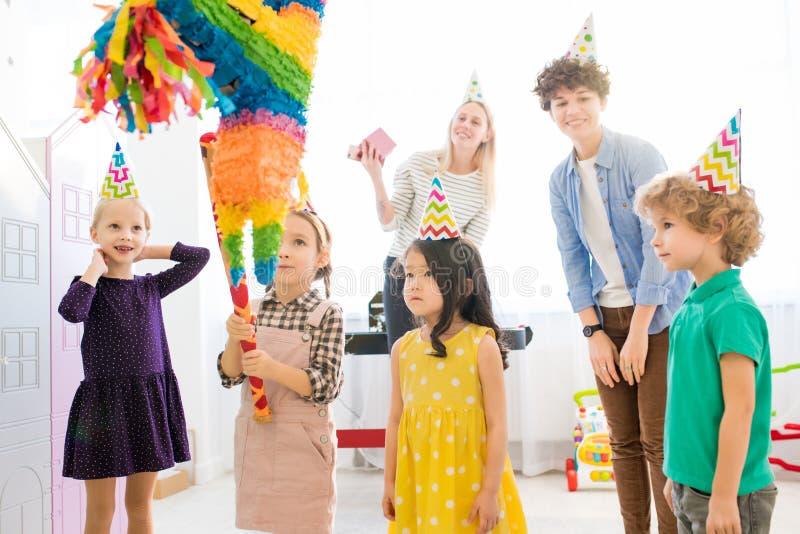 在生日宴会的女孩触击的彩饰陶罐 图库摄影