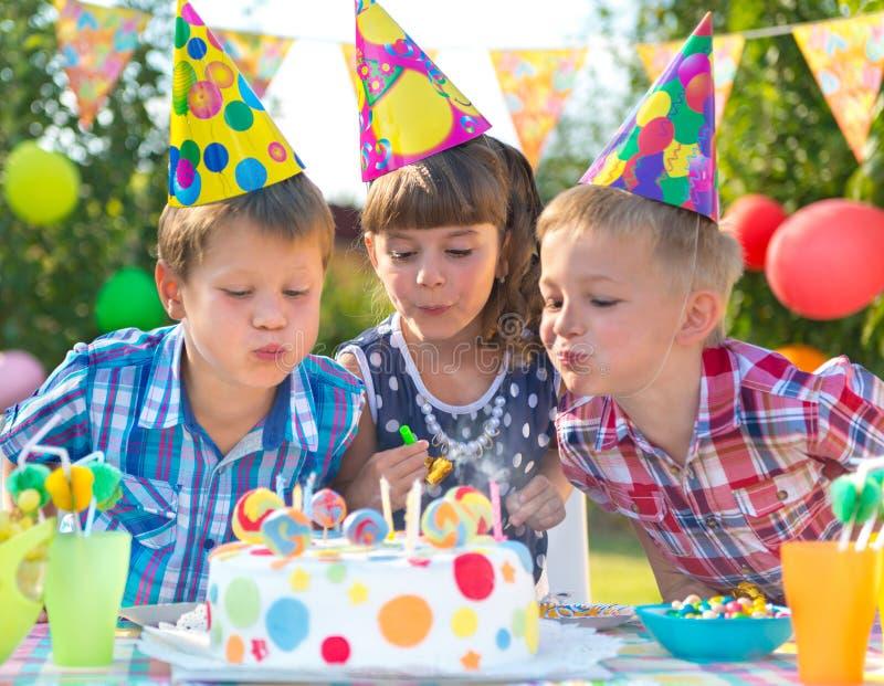 在生日聚会吹的蜡烛的孩子在蛋糕 库存图片