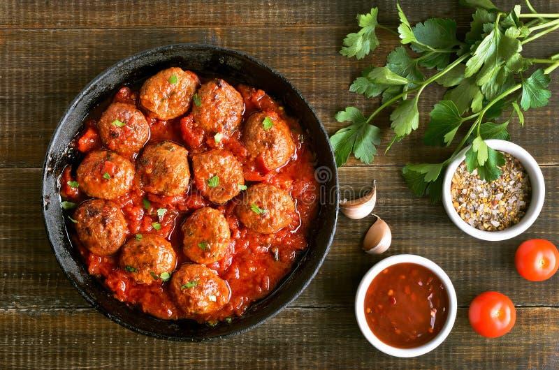 在生铁平底锅、新鲜的荷兰芹和蕃茄的丸子 库存图片