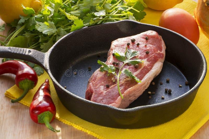 在生铁平底锅和被分类的菜的未加工的牛排 免版税图库摄影