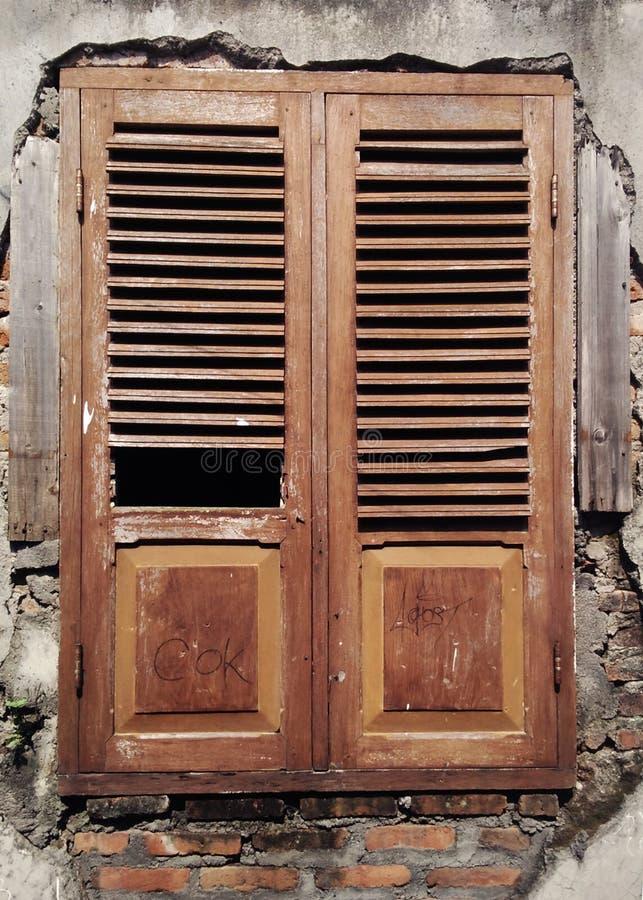在生锈的打破的和被破坏的墙壁上的老和地道窗口有抓痕和街道画的 免版税库存图片