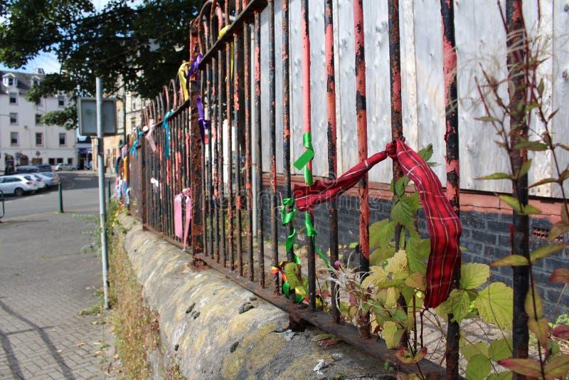 在生锈的栏杆的格子呢丝带 免版税库存图片
