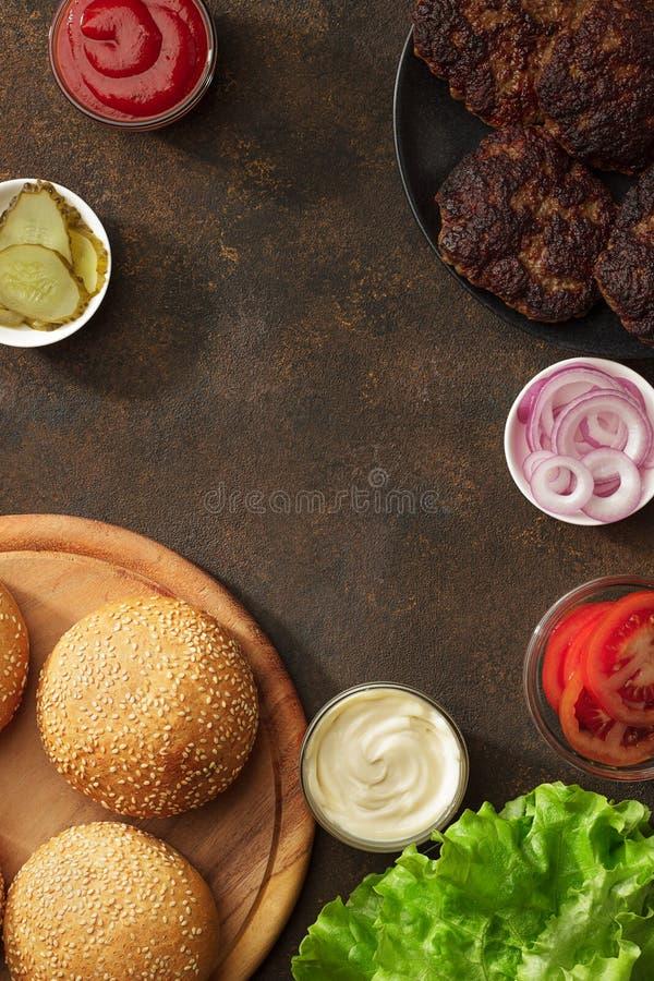 在生锈的背景的自创汉堡成份 库存图片