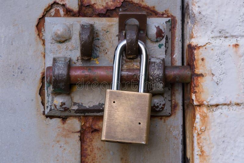 在生锈的被闩上的门的挂锁 免版税库存照片