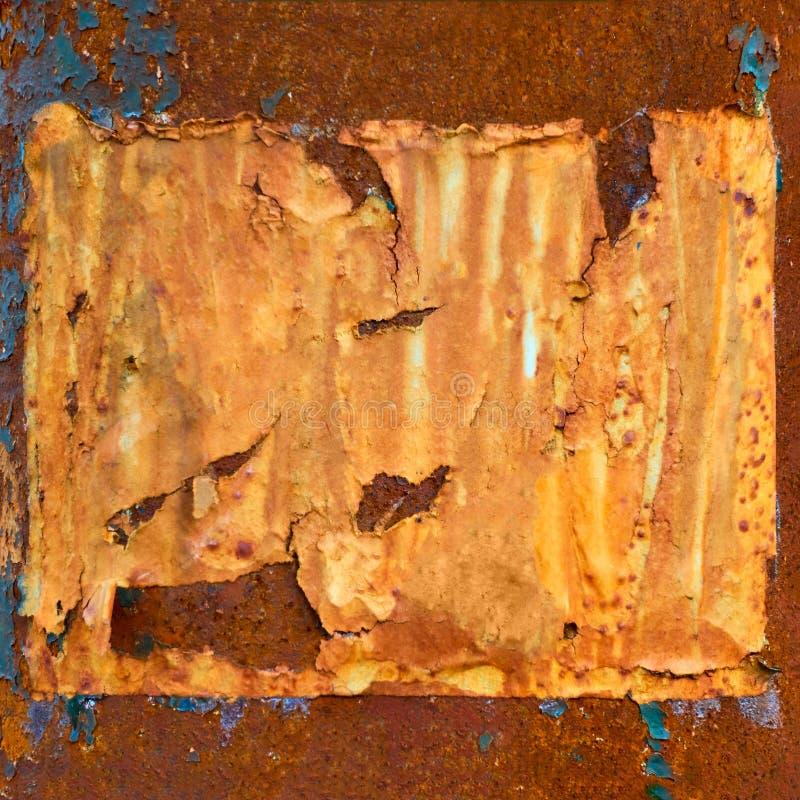 在生锈的金属墙壁上的老空白的被撕毁的纸 免版税库存图片