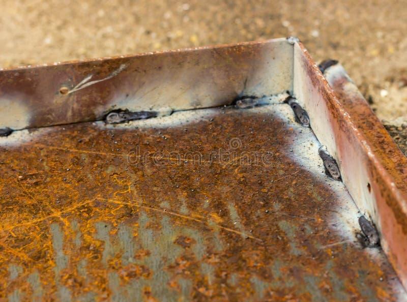 在生锈的金属的焊接缝 金属弯头被焊接对铁基地 免版税库存照片