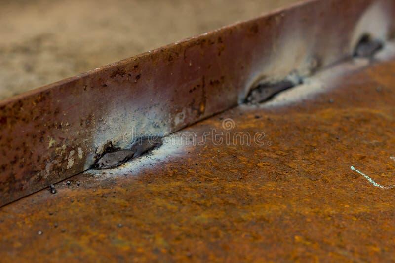 在生锈的金属的焊接缝 金属弯头被焊接对铁基地 库存图片