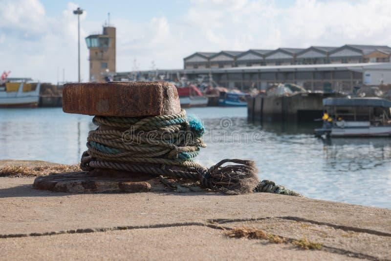 在生锈的金属附近被包裹的老,磨损的绳索停泊点,束缚渔船在港口 免版税图库摄影