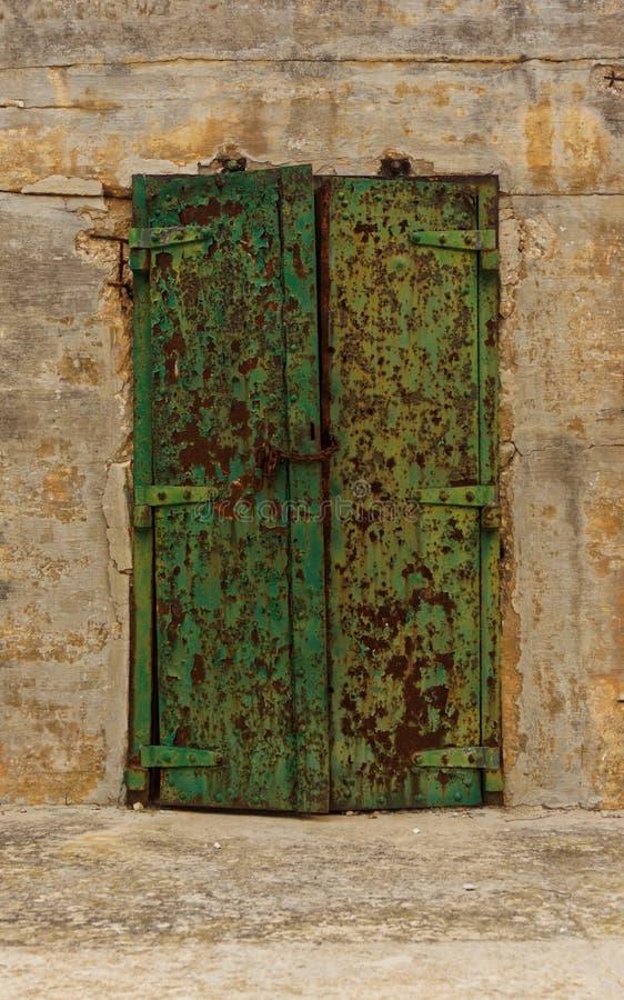 在生锈的门的老剥落的油漆 免版税库存图片