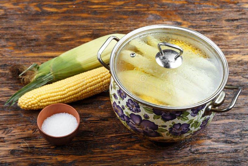 在用一个透明玻璃盒盖盖的平底深锅的未加工的玉米 免版税库存照片