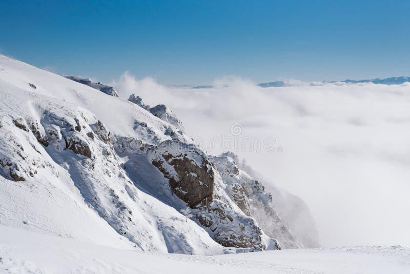 在用与一清楚的天空蔚蓝的雪盖的山顶部的峭壁在一好日子 库存照片