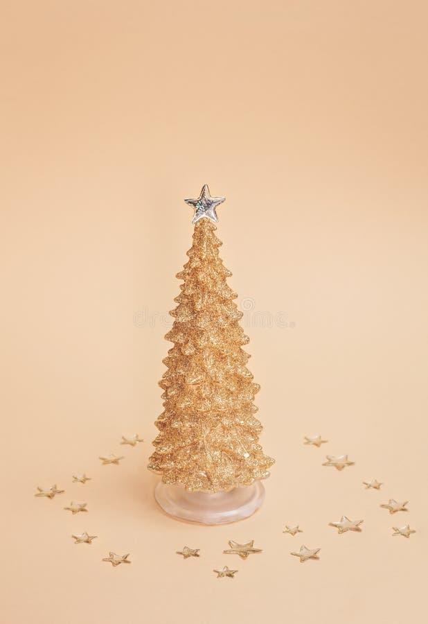 在用与压印的透明上面的发光的星装饰的淡色背景的金子闪耀的圣诞节松树 图库摄影