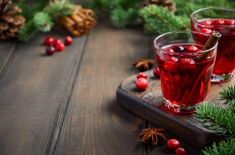 在用冷杉分支、香料和新鲜的莓果装饰的木背景的蔓越桔饮料 库存照片