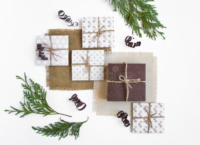 在用分支装饰的白色背景的土气手工制造礼物盒 顶视图,平的位置 免版税库存照片