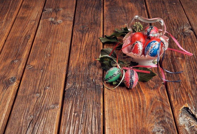 在用在葡萄酒,与空间的木桌的绿色常春藤分支装饰的一个古色古香的玻璃碗的手画复活节彩蛋 免版税库存图片