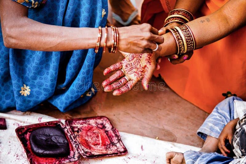 在用无刺指甲花纹身花刺装饰的过程的妇女手 免版税库存图片