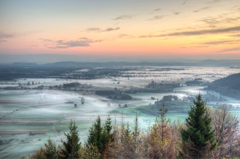 在用早晨薄雾报道的领域上的日出 免版税库存照片