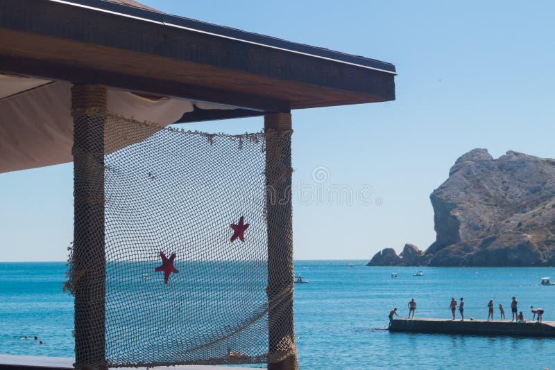 在用有海星的一个渔网装饰的阳台的部分的看法 有山和码头的海有人的 S 库存照片