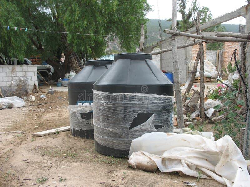 在用水泥涂的屋顶被烘干的塑料储水箱 库存图片