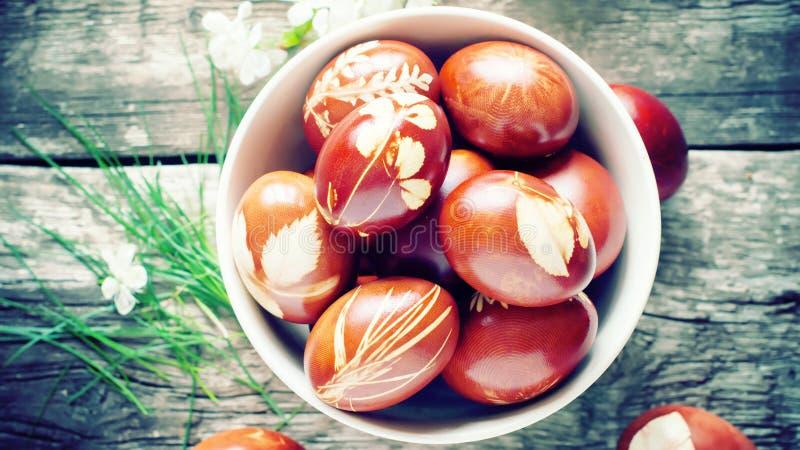在用自然新鲜的叶子装饰的木表上的复活节彩蛋 图库摄影