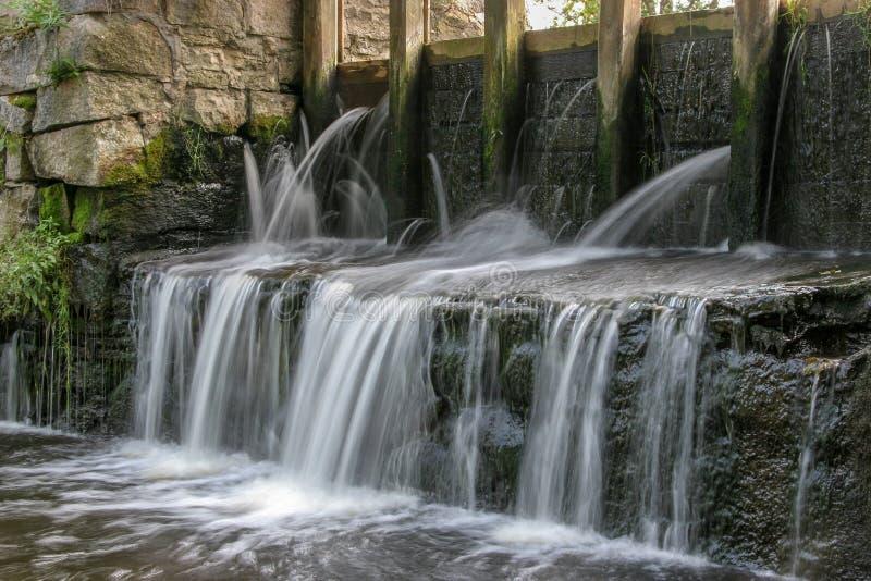 在用长的曝光和被弄脏的水射击的水车附近的小瀑布,象牛奶 免版税库存图片