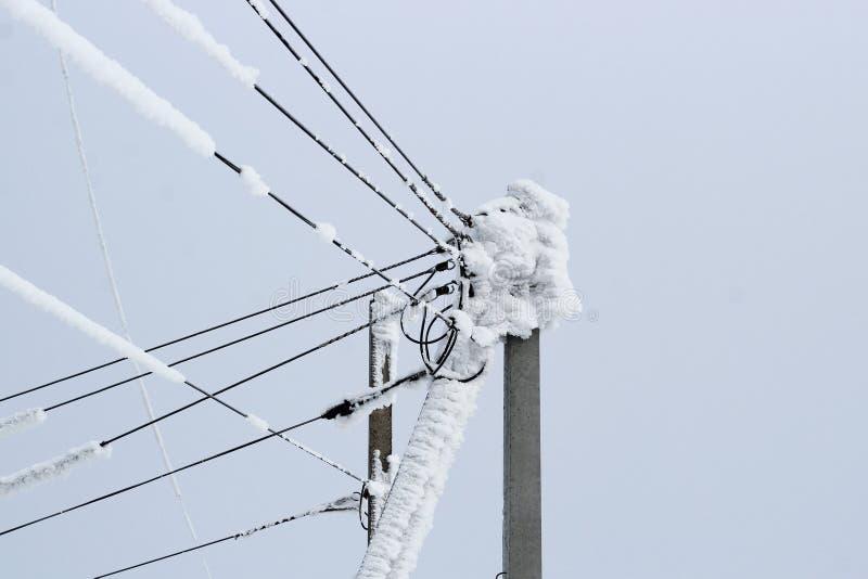 在用雪厚实的层数盖的许多导线杆的输电线  库存照片