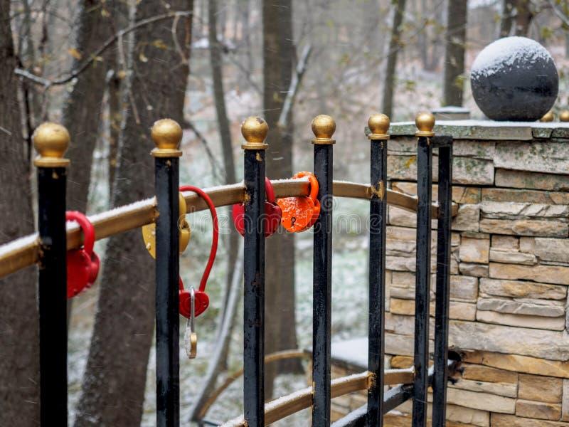 在用雪盖的篱芭格子的婚礼锁 库存照片