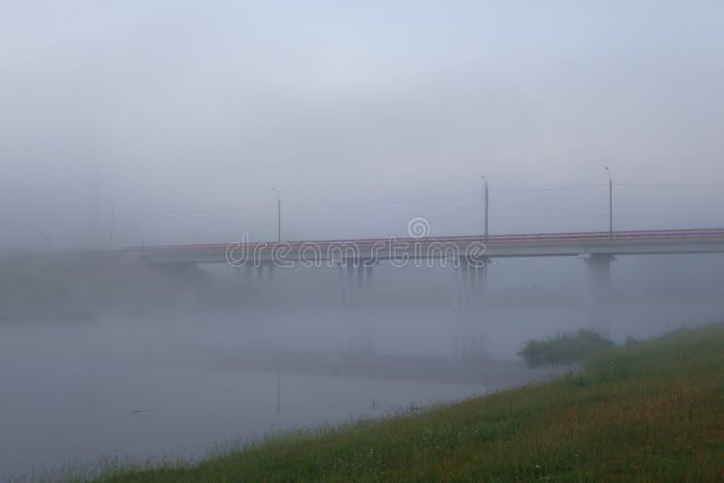 在用黎明前薄雾盖的河的路桥梁 库存照片