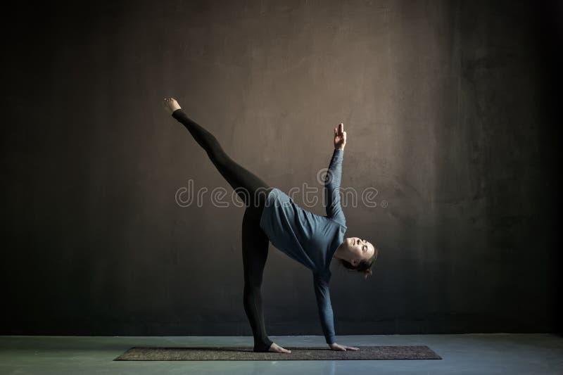 在甲晕锻炼,Ardha Chandrasana姿势的女子实践的瑜伽 库存照片