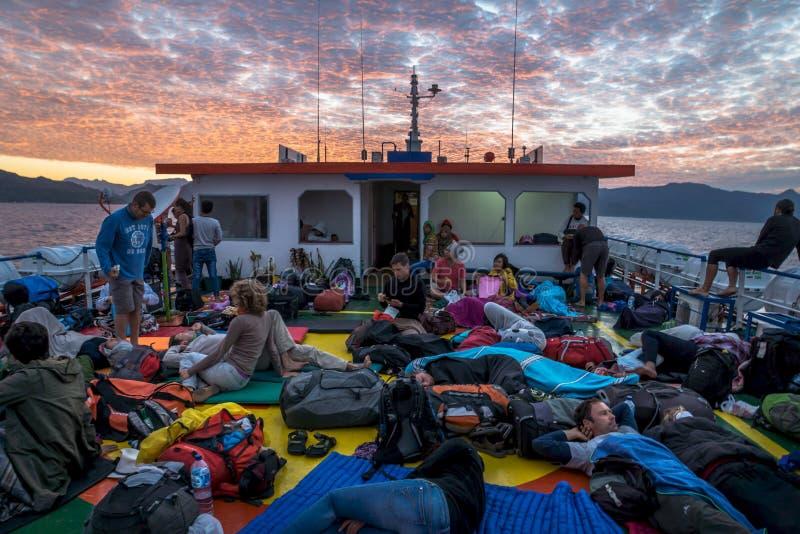 在甲板的日出有轮渡的睡觉的游人的从Wakai向哥伦打洛市,苏拉威西岛,印度尼西亚,亚洲 库存照片