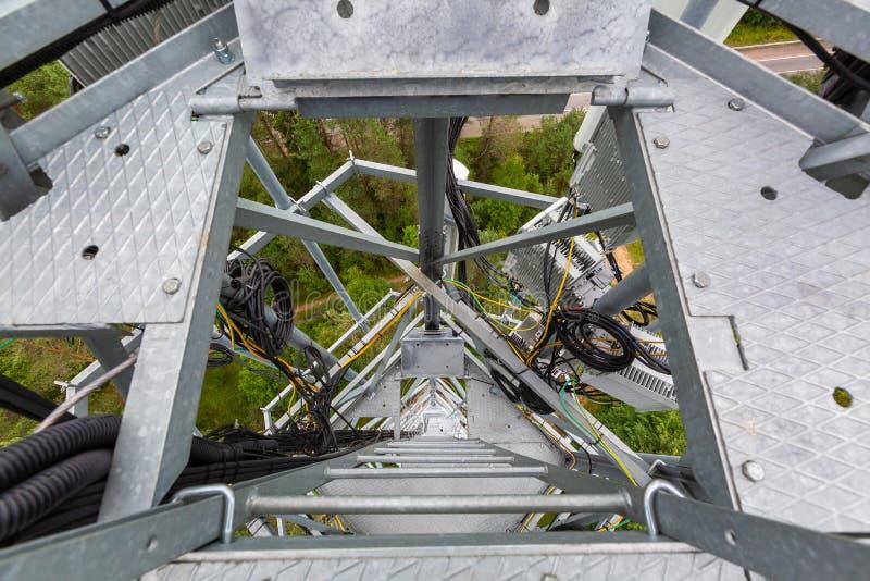 在电信塔的金属梯子和安装的天线用bas的室外通讯工具 库存图片