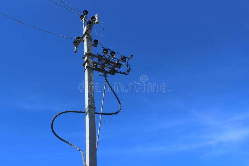 在电力量塔的高压电柱子缆绳在蓝天背景 送电线 免版税库存图片