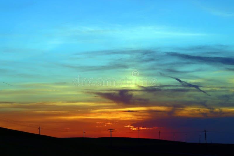 在电源杆后的五颜六色的日落在领域 免版税库存图片
