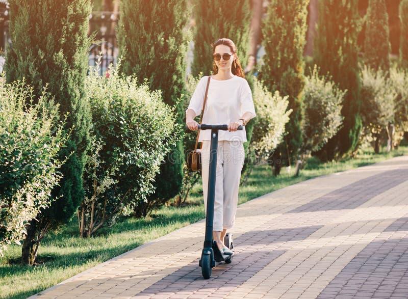 在电滑行车的女孩骑马在夏天公园 免版税库存照片