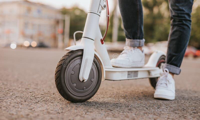 在电滑行车的庄稼腿在街道上 免版税库存照片