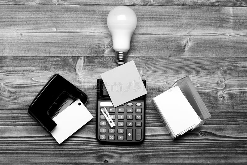在电灯泡、计算器和持卡者附近的打孔器 免版税库存照片