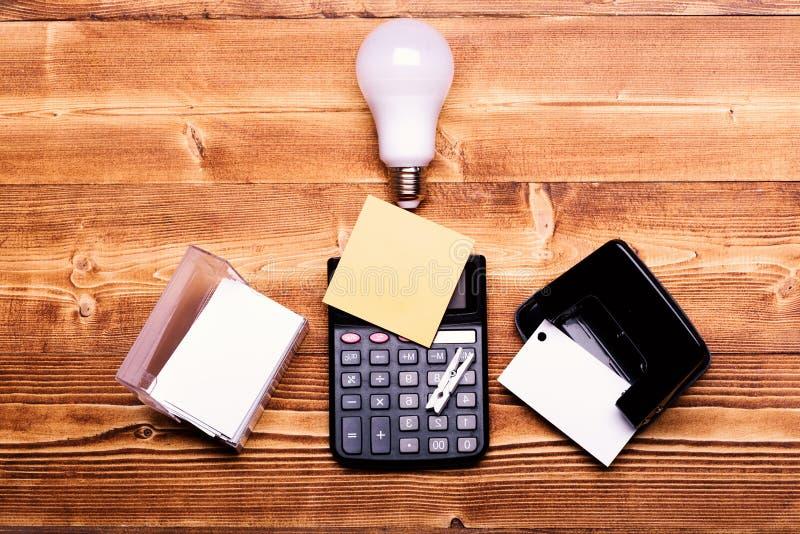 在电灯泡、计算器和持卡者附近的打孔器 免版税库存图片